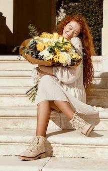 Mooie gelukkige vrouw buitenshuis met boeket van lentebloemen