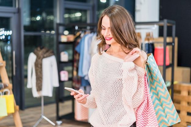 Mooie gelukkige vrouw die celtelefoon met behulp van bij een winkelcentrum