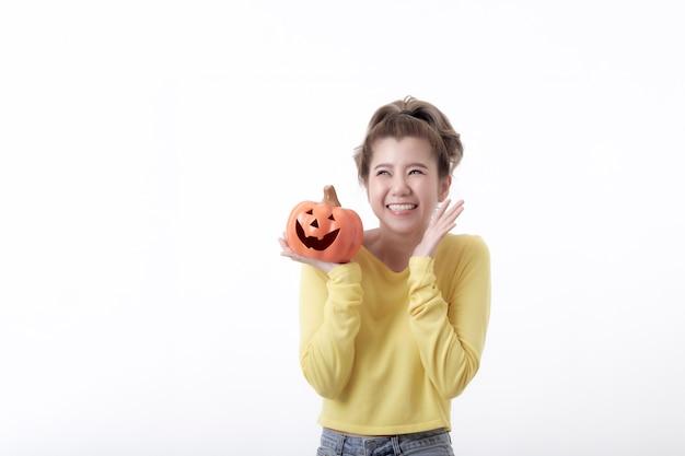 Mooie gelukkige vrouw die een pompoen in halloween-thema op witte achtergrond houdt