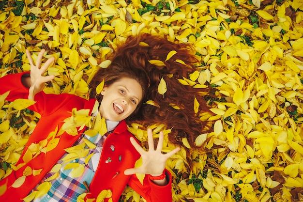 Mooie gelukkige vrouw die in gele de herfstbladeren legt.