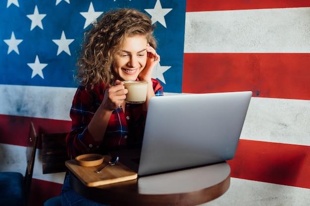 Mooie, gelukkige vrouw die laptop gebruikt terwijl ze in café zit. jonge vrouw die in een koffiewinkel zit en aan laptop werkt.