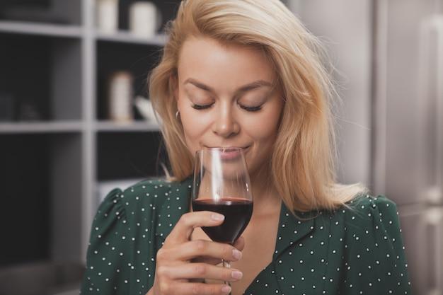 Mooie gelukkige vrouw die thuis hebbend glas wijn ontspannen