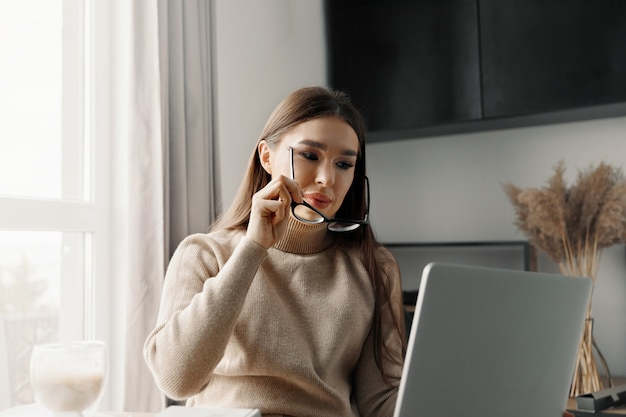 Mooie gelukkige vrouw die thuis met laptop werkt. glimlachende zakenvrouw die een bril draagt op kantoor met behulp van computer