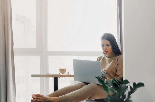 Mooie gelukkige vrouw die thuis met laptop werkt. glimlachende zakenvrouw op kantoor met behulp van computer