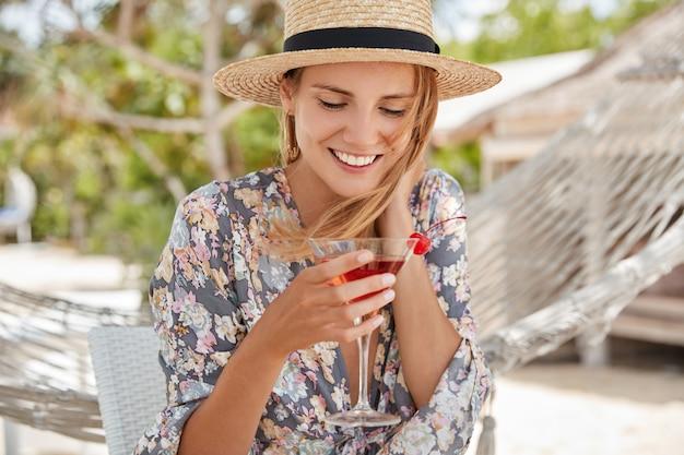 Mooie gelukkige vrouw draagt strohoeden en bloes met bloemenprint, recreëert alleen buiten tijdens het stralende zomerweer, drinkt een koude, verse cocktail, tevreden nadat ze in een hangmat ligt. recreatietijd