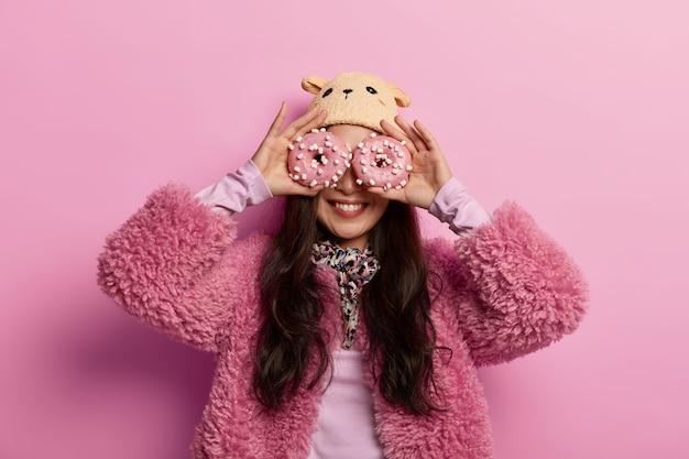 Mooie gelukkige vrouw draagt winter hoed en jas, houdt geglazuurde heerlijke donuts op de ogen, eet graag zoetwaren