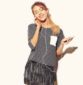 Mooie gelukkige vrouw in casual hipster zomer kleding geïsoleerd op wit luisteren muziek in smartphone met koptelefoon