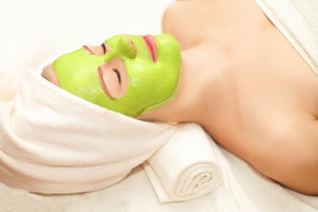 Mooie gelukkige vrouw in de spa die de behandeling van het gezichtsmasker maakt
