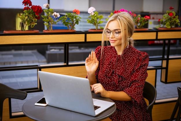 Mooie gelukkige vrouw in een rode jurk en glazen zitten in een café met een laptop communiceert via online communicatie