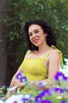 Mooie gelukkige vrouw in gele jurk poseren in de stad straat of park