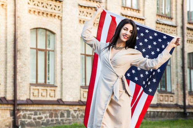 Mooie gelukkige vrouw met amerikaanse vlag die onafhankelijkheidsdag viert.