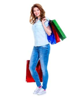 Mooie gelukkige vrouw met boodschappentassen in spijkerbroek geïsoleerd op een witte achtergrond