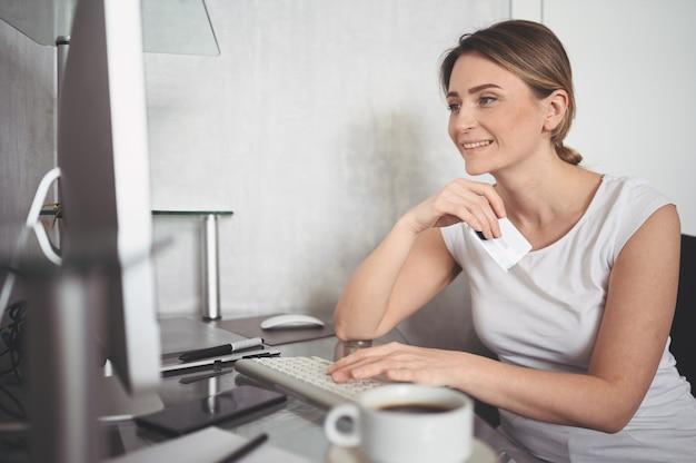 Mooie gelukkige vrouw met creditcard in de hand en met behulp van laptop computertoetsenbord. zakenvrouw of ondernemer werken. online winkelen, e-commerce, internetbankieren, zakgeldconcept