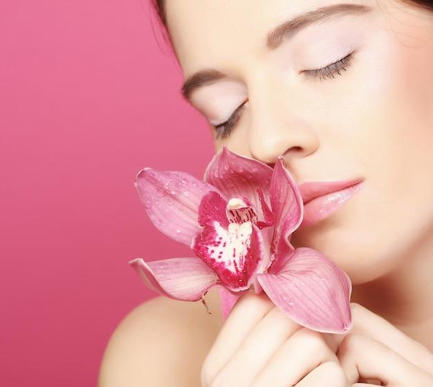 Mooie gelukkige vrouw met orchideebloem op roze