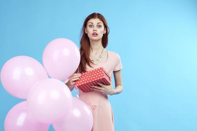 Mooie gelukkige vrouw met roze ballons en een gift