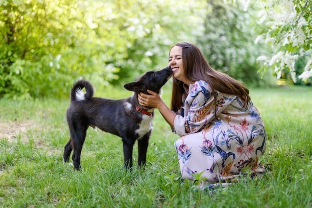 Mooie gelukkige vrouw met zwarte hond op verse groene weide en bos. ze omhelst en kust hem