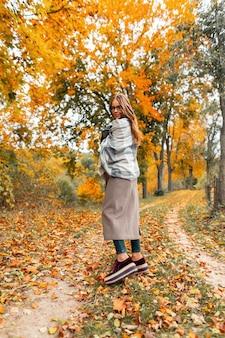 Mooie gelukkige vrouw model in een bril in een jas in rode schoenen in een gebreide sjaal geniet van ontspannen in het herfstpark onder een boom met oranje gebladerte. blij meisje staat in het park en lacht schattig. Premium Foto