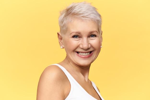 Mooie gelukkige vrouw van middelbare leeftijd met kort geverfd haar camera kijken met vrolijke brede glimlach, lachen om grappige grap.