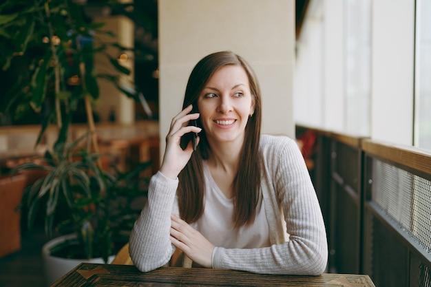 Mooie gelukkige vrouw zit alleen in de buurt van groot raam in de coffeeshop, ontspannen in restaurant tijdens vrije tijd. jonge vrouw met pratend gesprek met mobiele telefoon, rust in café. lifestyle-concept