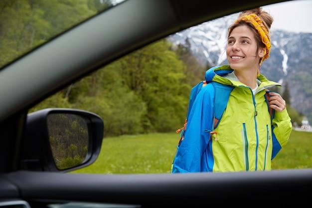 Mooie gelukkige vrouwelijke ontdekkingsreiziger vormt tegen hoge bergen en groen bos