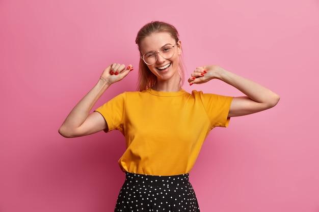 Mooie gelukkige vrouwelijke student glimlacht breed, knipoogt ogen en giechelt positief, viert succes