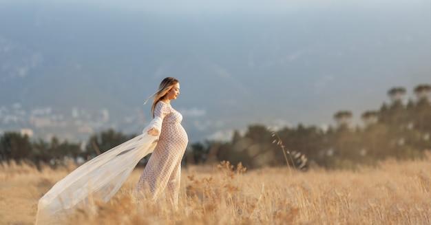 Mooie gelukkige zwangere vrouw in de zomerweide met in de zonsondergang cyprus Premium Foto