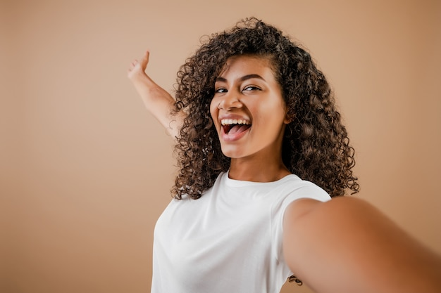 Mooie gelukkige zwarte jonge vrouw die selfie geïsoleerd over bruin maken