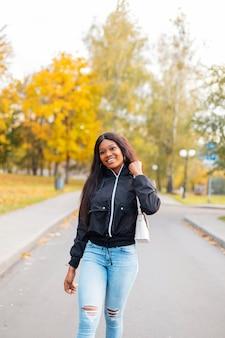 Mooie gelukkige zwarte vrouw in een modieus casual jasje met jeans en een handtas loopt in een herfstpark met felgeel blad