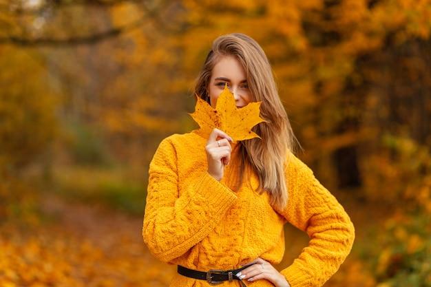 Mooie geluksvrouw in vintage gebreide trui bedekt haar gezicht met geel herfst esdoornblad en loopt in het park met herfst gouden blad