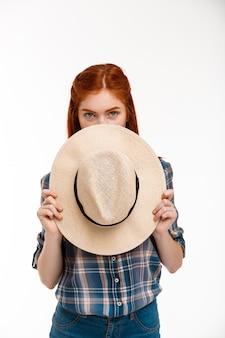 Mooie gember meisje met hoed over witte muur.