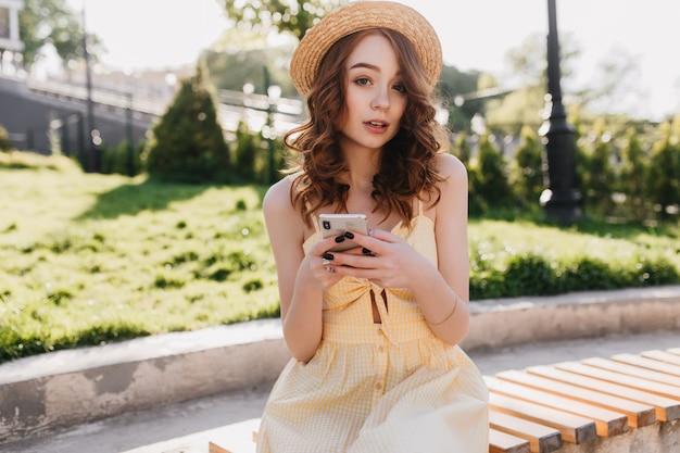Mooie gember meisje poseren tijdens het sms-bericht in de ochtend. buiten schot van fascinerende jonge vrouw in hoed zitten in park en genieten van zomerweer.