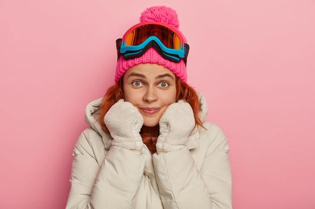 Mooie gember vrouw in winterkleding, geniet van buitensport, houdt beide handen in wanten onder de kin, kijkt verrassend naar camera met groene ogen, model tegen roze achtergrond.