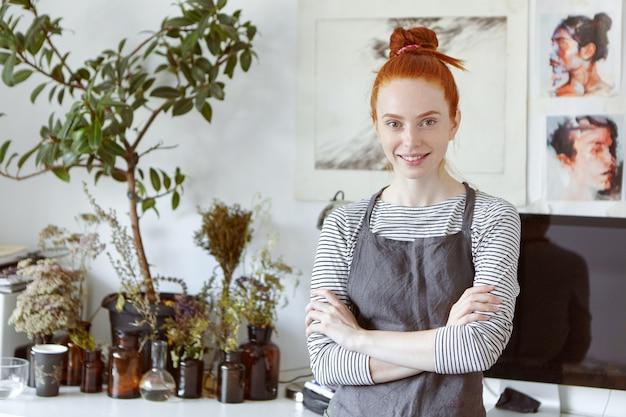 Mooie gember vrouw studeren kunst in werkplaats, zachtjes glimlachend, gekruiste handen staan tegen prachtige foto's.