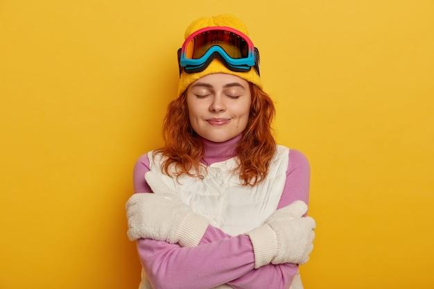 Mooie gember vrouw voelt koud na buitenactiviteiten, verwarmt zichzelf met omhelzing, draagt gele hoed, wit vest en handschoenen, sluit ogen, geïsoleerd op gele achtergrond