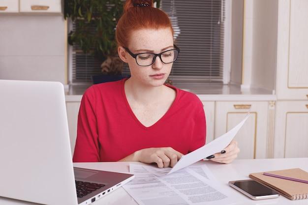 Mooie gember vrouwelijke freelancer werkt ver thuis, bestudeert documenten, zit achter geopende laptop