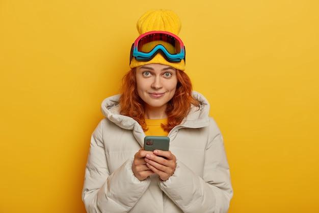 Mooie gembervrouw plaatst foto's op sociale netwerken na een geweldige dag, heeft actieve rust in de winter, houdt mobiele telefoon vast, draagt hoed, jas en beschermende skibril, poseert over gele muur