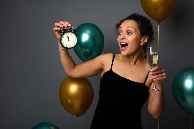 Mooie gemengd ras vrouw in zwarte fluwelen avondjurk poseren met wekker en glas mousserende wijn tegen glanzend groen metallic en gouden lucht ballonnen op grijze achtergrond met ruimte voor advertentie