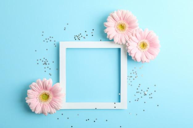 Mooie gerbera's en frame op kleur achtergrond, ruimte voor tekst