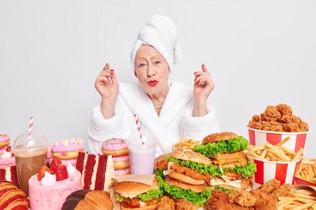 Mooie gerimpelde dame geniet van een cheatmealdag omringd door junkfood