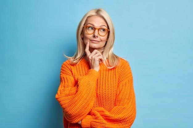 Mooie gerimpelde vrouw van middelbare leeftijd houdt wijsvinger op wang staat in bedachtzame pose dagdromen over iets dat een gebreide trui draagt.