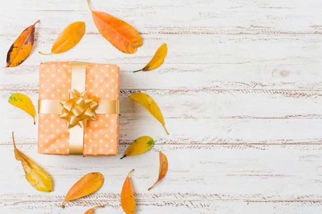 Mooie geschenkdoos en herfstbladeren boven tafel met ruimte voor tekst