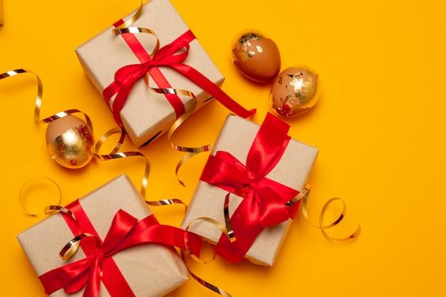 Mooie geschenkdozen met rode strikken en snoepjes op een beige achtergrond voor een site, banner of artikel