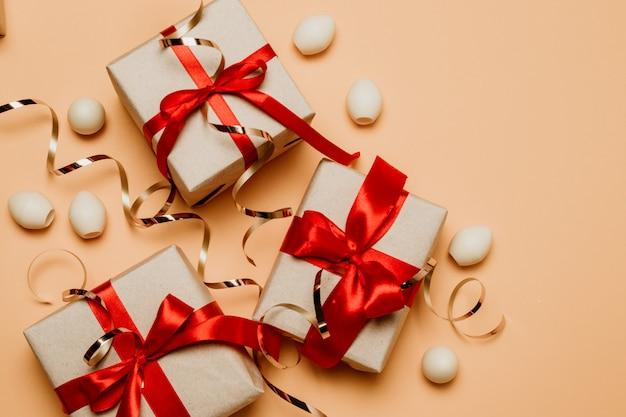 Mooie geschenkdozen met rode strikken en snoepjes op een beige achtergrond