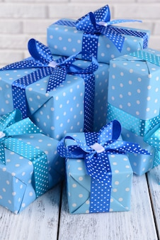 Mooie geschenken op tafel op bakstenen muur achtergrond