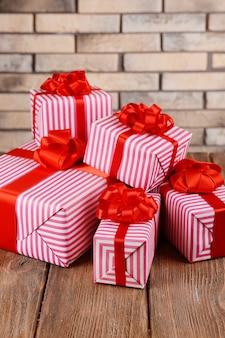 Mooie geschenken op tafel op bakstenen muur