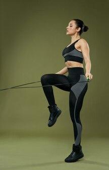 Mooie geschikte jonge vrouw die over touwtjespringen springt
