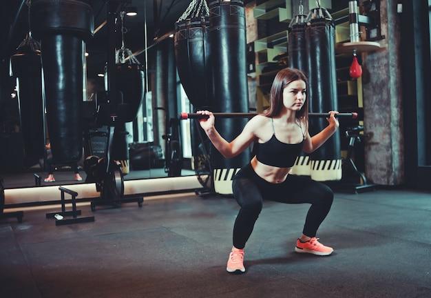 Mooie geschikte vrouw die hurkzitoefening met gymnastiek- stok doen bij in dozen doende gymnastiek