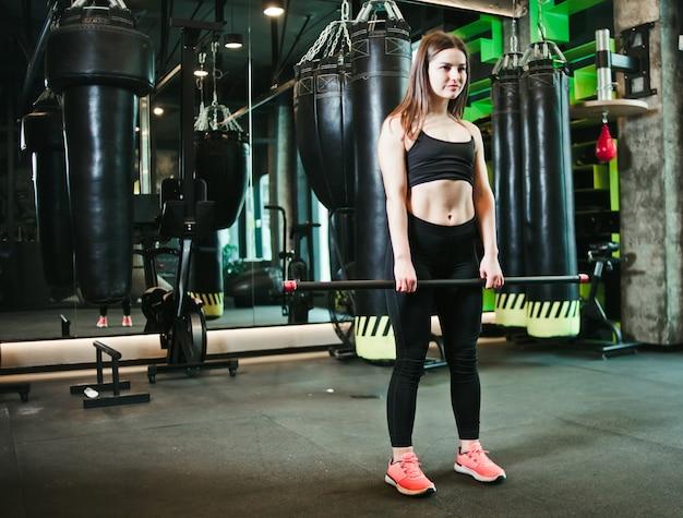 Mooie geschikte vrouw die oefening met gymnastiek- stok doen bij het in dozen doen gymnastiek