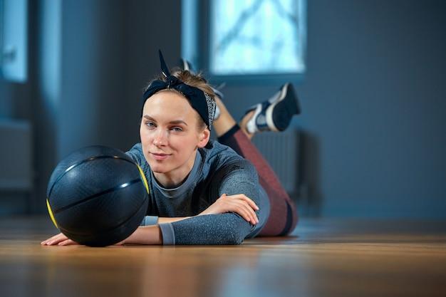 Mooie geschikte vrouw in sportkleding die terwijl het liggen op de vloer met basketbal voor venster bij levensstijl van het gymnastiek het gezonde meisje en sportconcept stellen