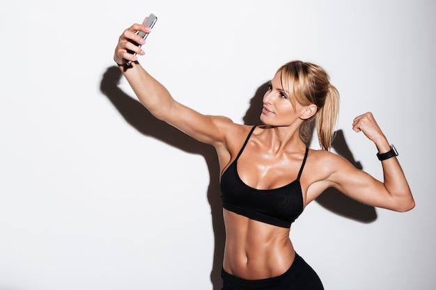 Mooie geschiktheidsvrouw die een selfie neemt